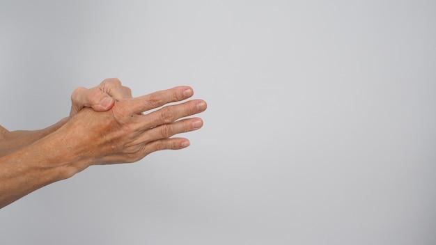 Mulher idosa ou idosa com dor de dedo e mão em fundo branco. que teve artrite ou dedos em gatilho