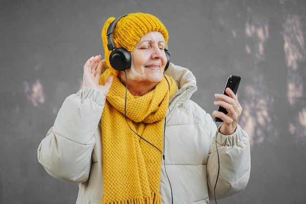 Mulher idosa ouvindo música contra a parede violeta.