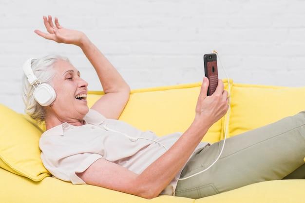 Mulher idosa ouvindo música no fone de ouvido
