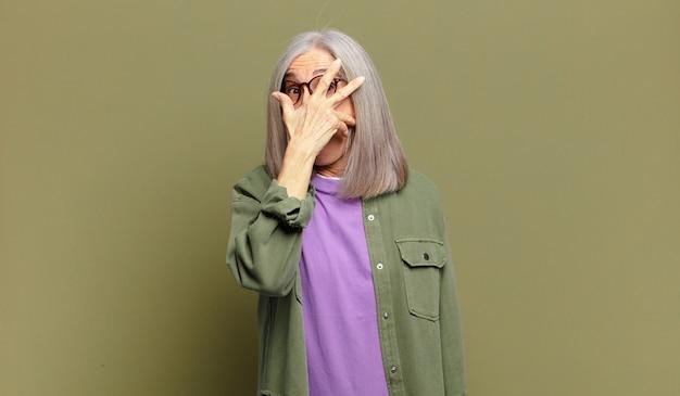 Mulher idosa parecendo chocada, assustada ou apavorada, cobrindo o rosto com a mão e espiando por entre os dedos