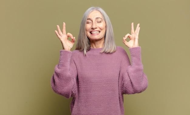 Mulher idosa parecendo concentrada e meditando, sentindo-se satisfeita e relaxada, pensando ou fazendo uma escolha