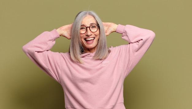Mulher idosa parecendo feliz, despreocupada, amigável e relaxada curtindo a vida e o sucesso, com uma atitude positiva