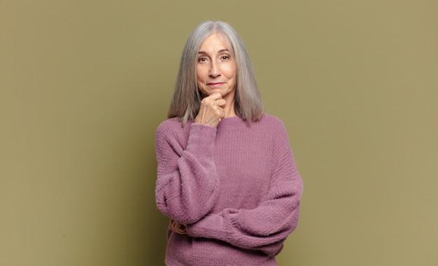Mulher idosa parecendo feliz e sorrindo com a mão no queixo, pensando ou fazendo uma pergunta, comparando opções
