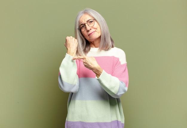 Mulher idosa parecendo impaciente e zangada, apontando para o relógio, pedindo pontualidade, quer ser pontual