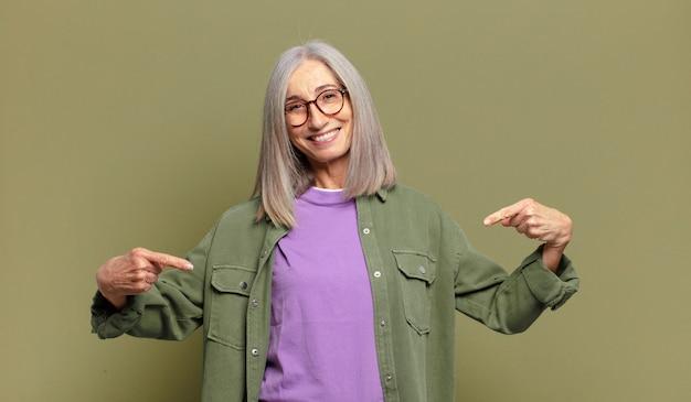 Mulher idosa parecendo orgulhosa, arrogante, feliz, surpresa e satisfeita, apontando para si mesma, sentindo-se uma vencedora
