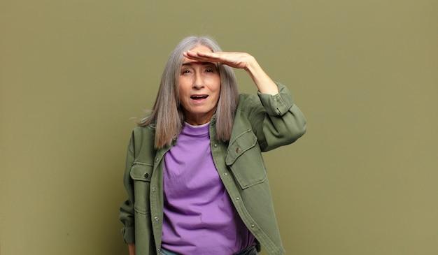 Mulher idosa parecendo perplexa e atônita, com a mão na testa olhando para longe, observando ou procurando