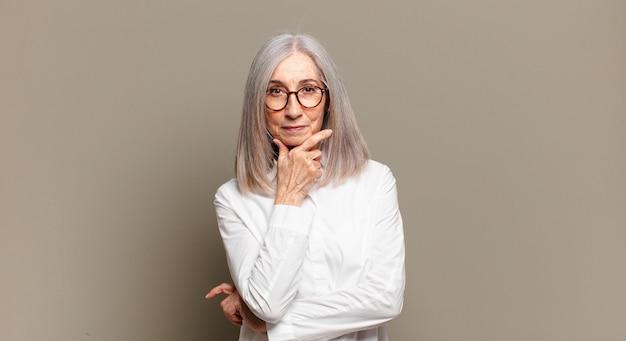 Mulher idosa parecendo séria, pensativa e desconfiada, com um braço cruzado e a mão no queixo, opções de peso