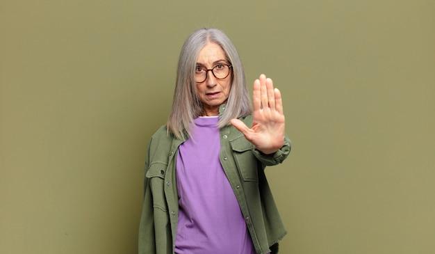 Mulher idosa parecendo séria, severa, descontente e irritada, mostrando a palma da mão aberta fazendo gesto de pare