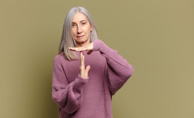 Mulher idosa parecendo séria, severa, irritada e descontente, fazendo sinal de tempo limite