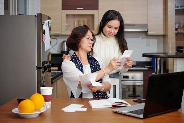 Mulher idosa pedindo à filha adulta que a ajude a pagar contas e administrar as finanças domésticas
