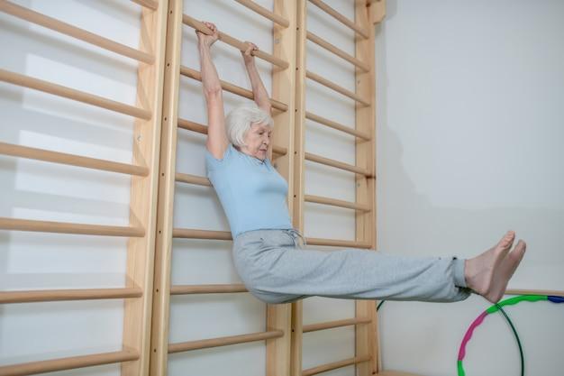 Mulher idosa pendurada em uma escada na parede