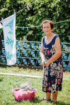 Mulher idosa pendurando roupa em uma bacia no quintal