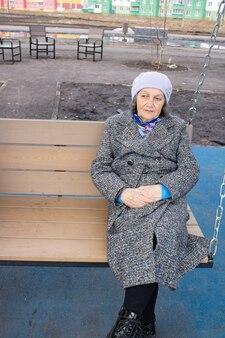 Mulher idosa pensativa com um casaco sentada em um balanço ao ar livre na primavera.
