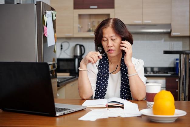 Mulher idosa pensativa mordendo o braço da armação dos óculos quando está sentada à mesa da cozinha e lendo informações em sua agenda ou diário e fazendo uma ligação