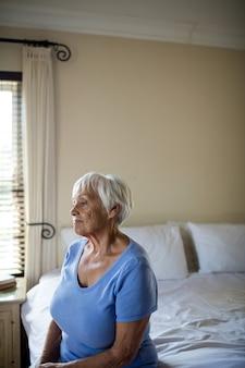 Mulher idosa pensativa, sentada na cama no quarto de casa