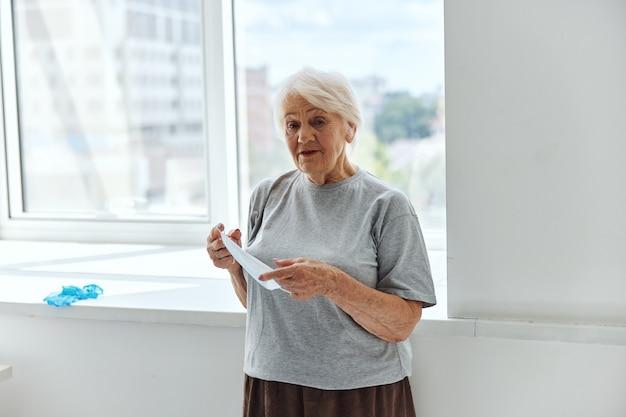 Mulher idosa perto de janela máscara médica de proteção de hospital