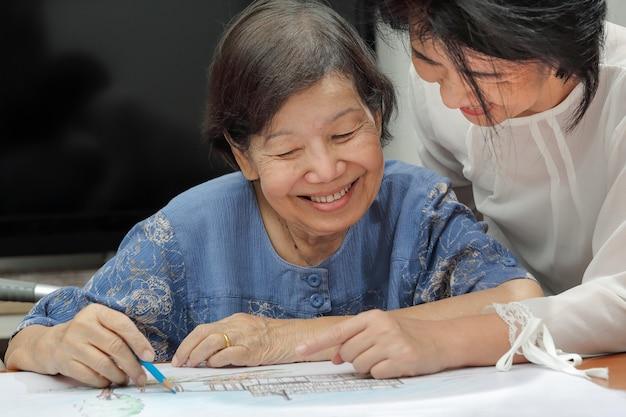 Mulher idosa pintando a cor em seu desenho com a filha, hobby em casa