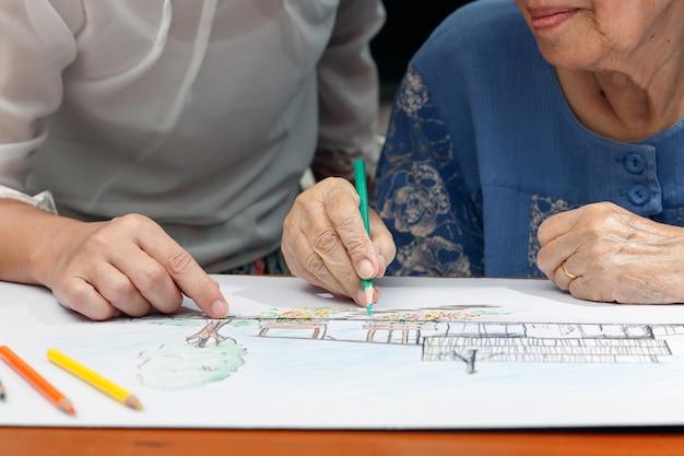 Mulher idosa pintando a cor em seu desenho com a filha, passatempo em casa