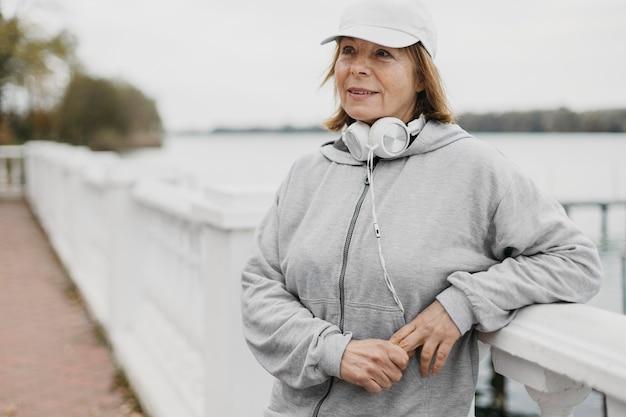Mulher idosa posando ao ar livre com fones de ouvido