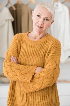 Mulher idosa posando com braços cruzados e sorrindo