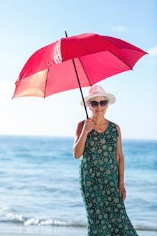 Mulher idosa posando com um guarda-chuva