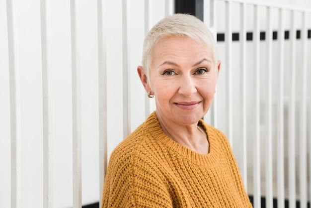 Mulher idosa posando e sorrindo com espaço de cópia