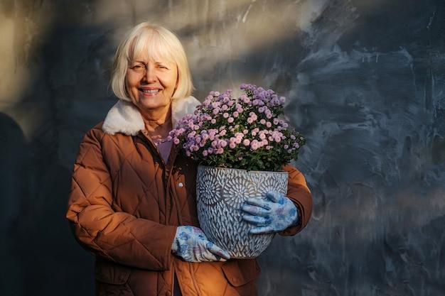 Mulher idosa positiva carregando flores em vasos enquanto representa o hobby e o conceito de jardinagem Foto Premium