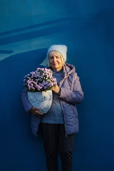 Mulher idosa positiva carregando flores em vasos enquanto representa o hobby e o conceito de jardinagem