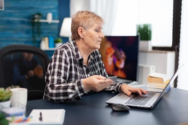 Mulher idosa positiva pagando contas segurando um cartão de crédito de plástico