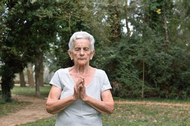 Mulher idosa, prática, ioga, ao ar livre