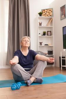 Mulher idosa praticando ioga em casa por uma vida saudável.
