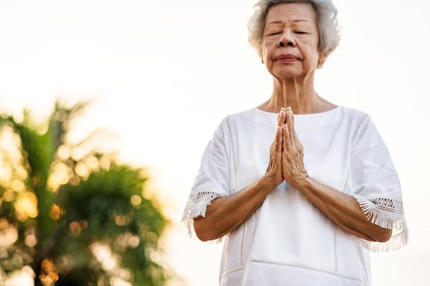 Mulher idosa praticando ioga pela manhã