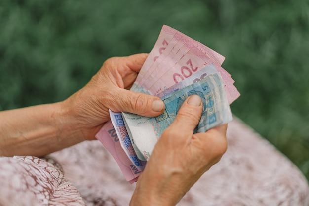Mulher idosa preocupada contando hryvnia dinheiro ucraniano. o conceito de velhice, pobreza, austeridade.
