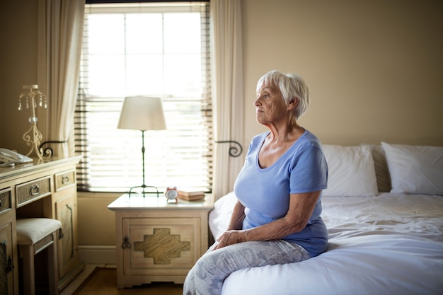 Mulher idosa preocupada sentada na cama no quarto de casa