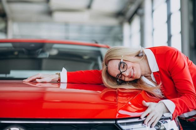 Mulher idosa que abraça um automóvel móvel em uma sala de exposições do carro