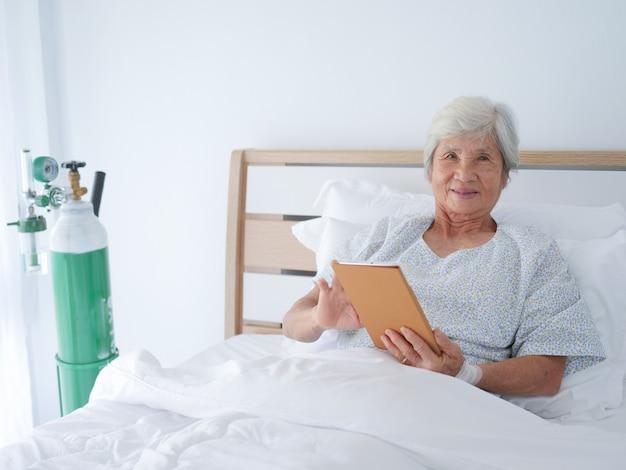 Mulher idosa que coloca na cama de hospital.