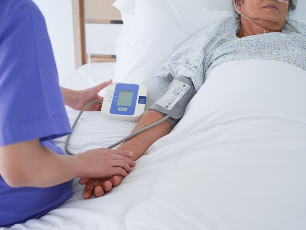 Mulher idosa que encontra-se na cama de hospital.