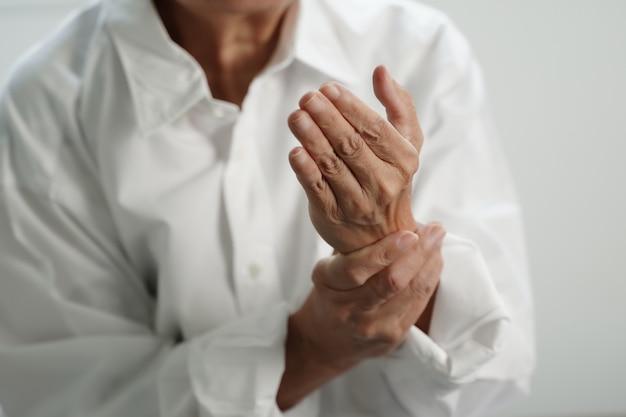 Mulher idosa que sofre de dor de artrite reumatóide