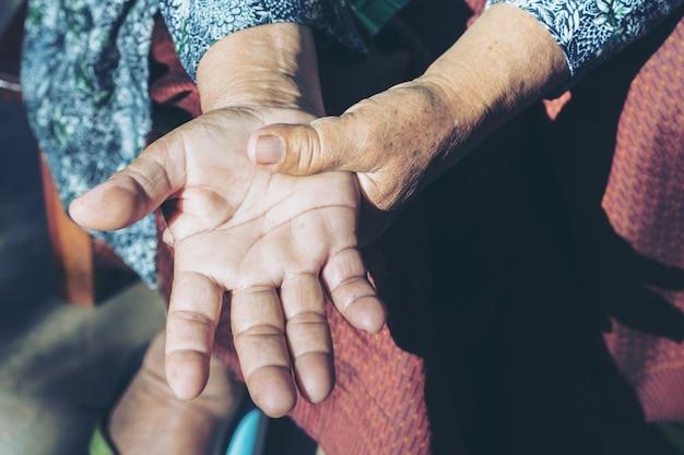 Mulher idosa que sofre de dor na mão.