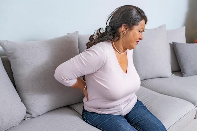 Mulher idosa que sofre de dor nas costas em casa