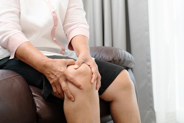 Mulher idosa que sofre de dor no joelho em casa