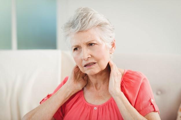 Mulher idosa que sofre de dor no pescoço em casa