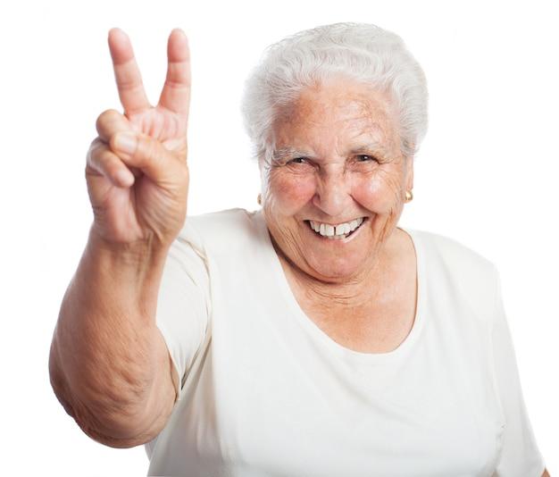 Mulher idosa que sorri com dois dedos levantados