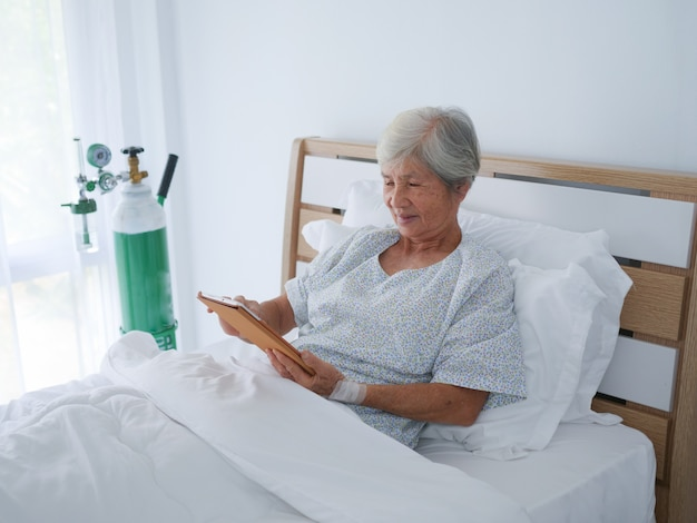 Mulher idosa que usa o portátil na sala de hospital.