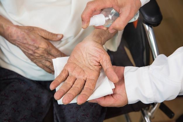 Mulher idosa recebe uma máscara do cuidador para se proteger do coronavírus covid-19