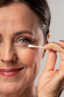 Mulher idosa removendo maquiagem com cotonete