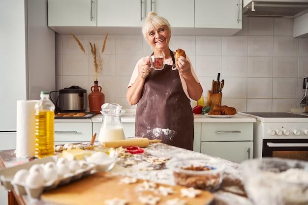 Mulher idosa satisfeita degustando produtos de confeitaria caseiros