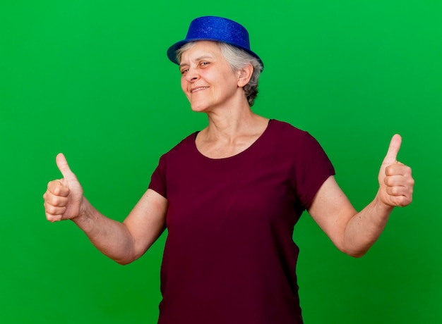 Mulher idosa satisfeita usando chapéu de festa com as duas mãos no verde