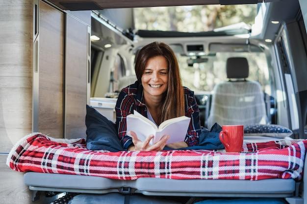 Mulher idosa se divertindo dentro de uma van enquanto lê um livro e bebe café - foco no rosto