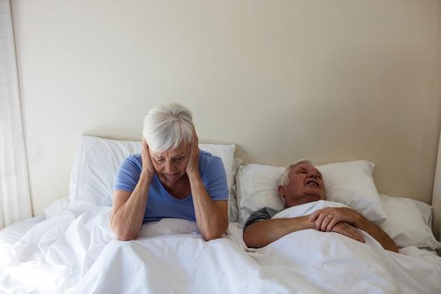 Mulher idosa se incomodando com homem roncando na cama do quarto